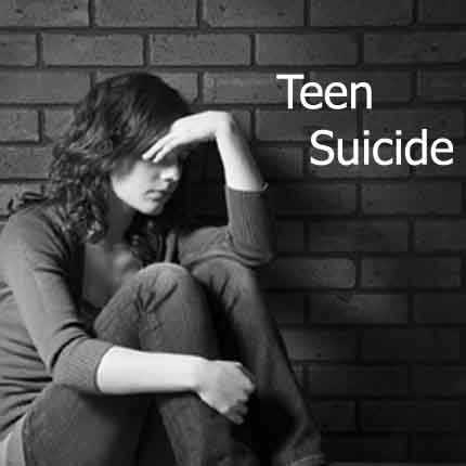 Teenage girl sitting against brick wall in depressed state